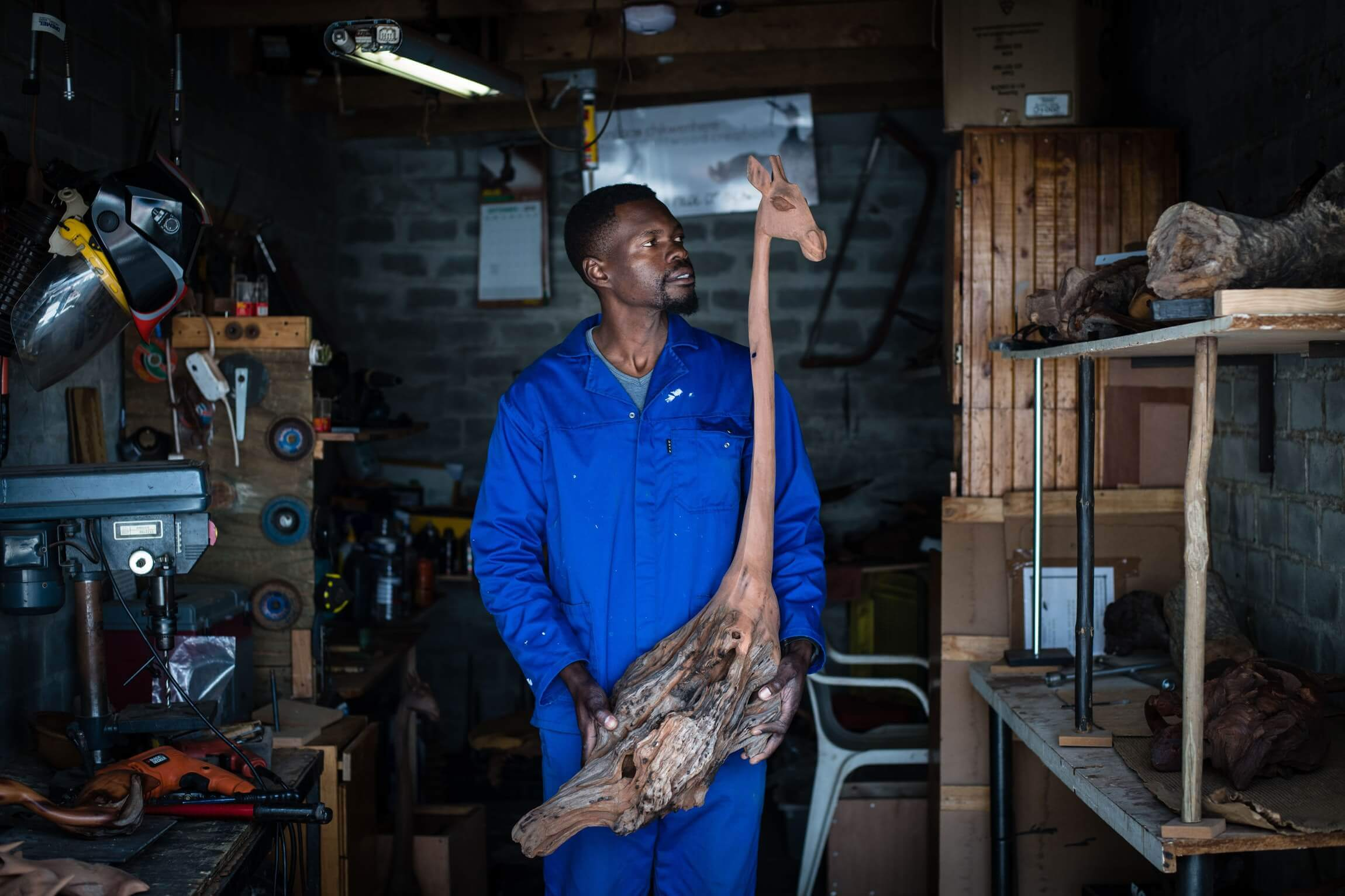 Boniface holding up a partially completed giraffe sculpture.