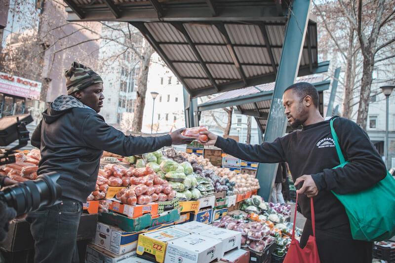Jabu Mdluli of Unwrapped buying produce at the market.