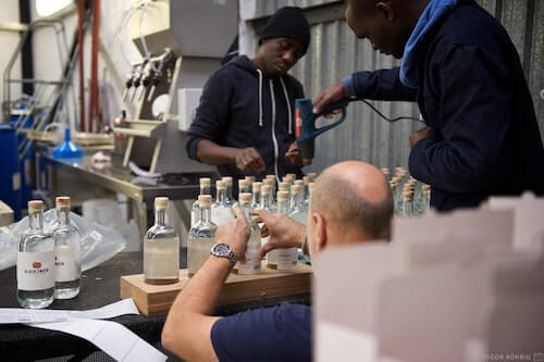 Preparing the gin bottles for labelling and packaging.