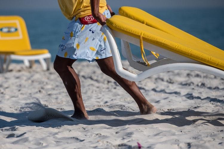 Moving beach chairs on Cape Town beach.