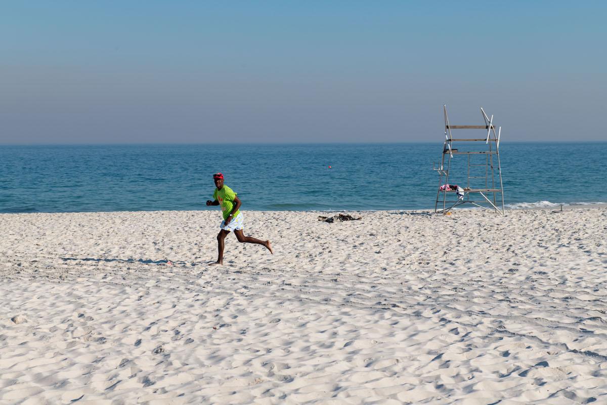 A vendor running across a Cape Town beach.