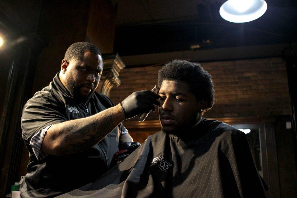 A barber cutting his customer's hair.