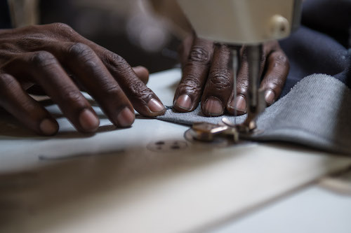 Achmed the tailor moving fabric into the sewing machine.