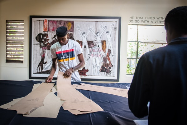 Tshepo Mohlala measuring and cutting denim to make jeans.