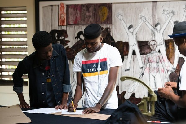 Tshepo working with the junior tailor to make a pair of jeans.