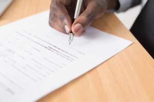 An image of a lawyer signing a contract for a new small business.