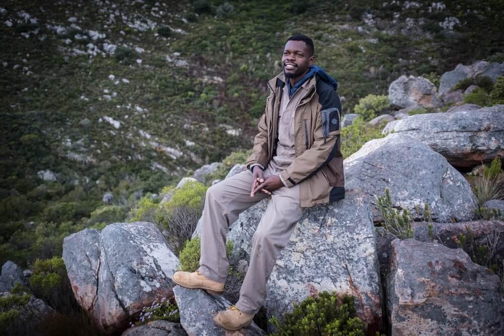 Boniface posing for a portrait on a boulder.