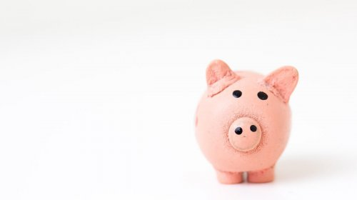 An image of a piggy bank in an article about using personal accounts for business.